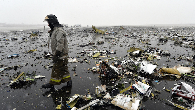 TOPSHOT - Russian emergency rescuer walks through wreckage of the flydubai passenger jet which crashed, killing all 62 people on board as it tried to land in bad weather in the city of Rostov-on-Don on March 19, 2016.  The plane, which came from Dubai, was making its second attempt to land when it missed the runway, erupting in a huge fireball as it crashed, leaving debris scattered across a wide area. The ministry said more than 700 rescuers and 100 vehicles were combing the area in driving wind and snow where the wreckage was strewn, with investigators confirming one of the plane's black boxes had been retrieved.  / AFP / -        (Photo credit should read -/AFP/Getty Images)